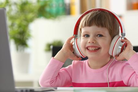 Little girl wearing headphones use mobile computer