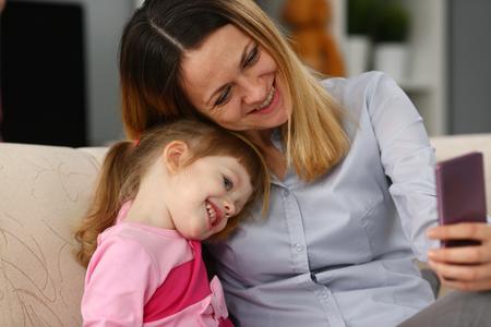 Moeder en haar dochtertje gebruiken mobiele telefoon om broers en zussen te bellen
