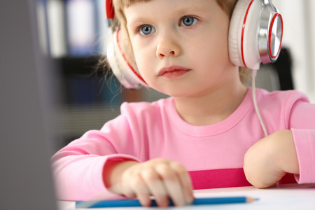 Little girl wearing headphones use mobile computer Standard-Bild - 122920410