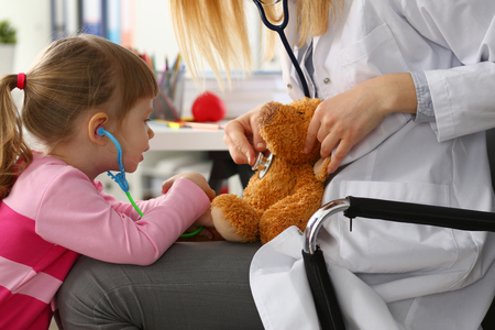 Little girl hold in arms toy stethoscope playing with teddy bear