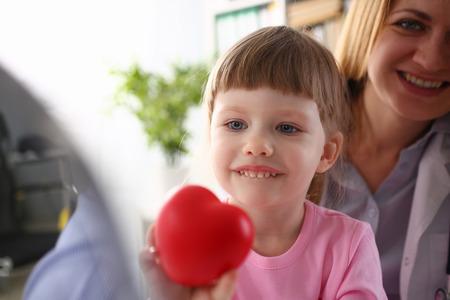 Médico visitante de niña bebé sosteniendo en las manos corazón de juguete rojo