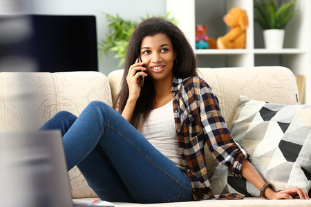 Smiling black woman hold in hand mobile phone at home Stock Photo