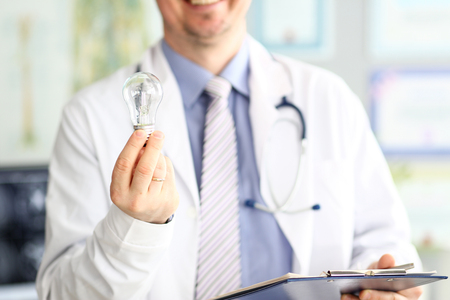 Male doctor hand holding lightbulb as bright idea invention symbol