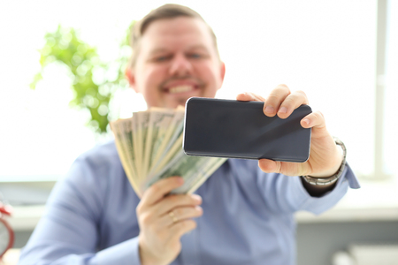 Man making self photo with mobile phone camera posing with pile of money Фото со стока