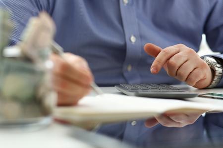 Männliche Hand, die den Taschenrechner verwendet, der finanzielle Ausgaben zählt