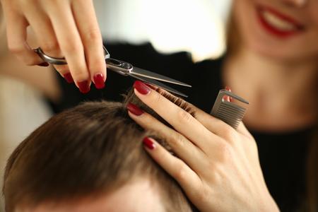 Friseur mit Schere schneidet braunes Männerhaar Standard-Bild