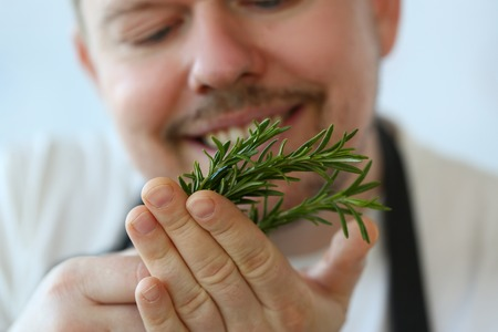 Smiling Chef Holding Green Rosemary Herb Bunch