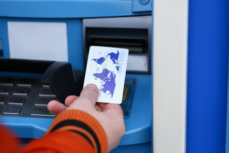 Male hand hold credit card aganist ATM Stock Photo