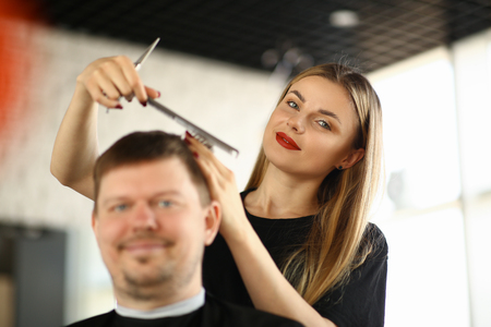 Female Hairdresser Combing Male Client in Salon Stockfoto