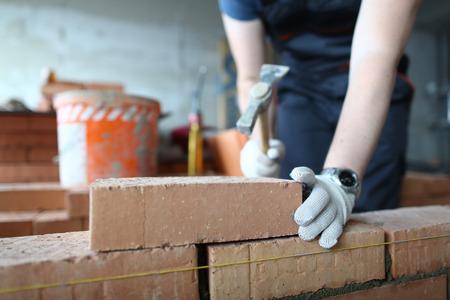 Skilled bricklayer putting red block