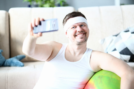 Smiling Sportsman Taking Photography on Smartphone Stockfoto