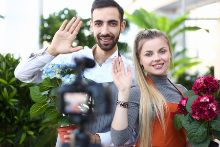 Man and Woman Blogger with Flower Waving to Camera