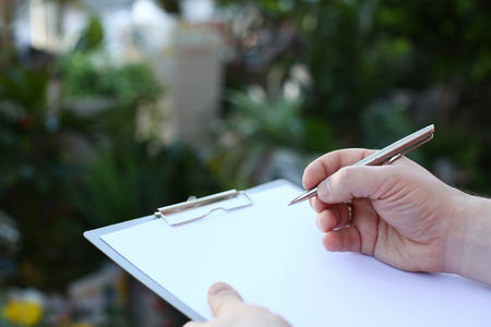 Human Hand Writing on Clipboard with White Paper Stockfoto