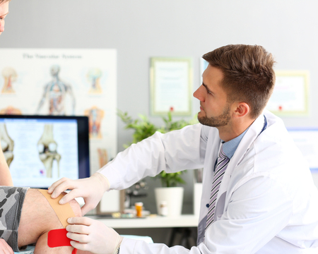 Handsome therapist helping patient