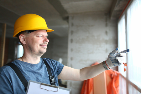 Laughing builder in gloves