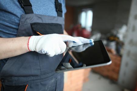 Builder holding modern tablet