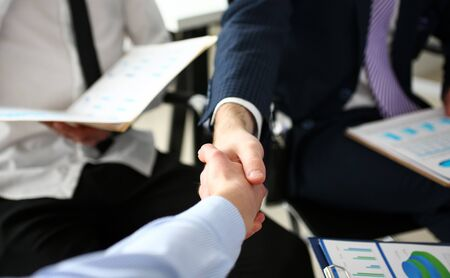 Group of businessmen shaking hands after productive meeting