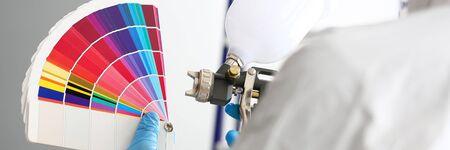 エアブラシとカラフルなファンテールピッキングウォールトーンを持つ職人の手 写真素材