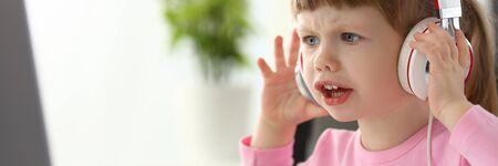 Little girl wearing headphones using computer aggressive articulating
