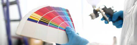 エアブラシとカラフルなファンテールを持つ職人の手は、塗装する壁のトーンを選ぶ
