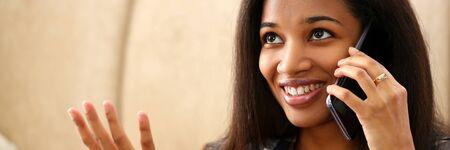 La donna di colore sorridente tiene in mano il telefono cellulare a casa