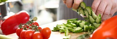 Professioneller Koch, der frische Gurken von Hand hackt