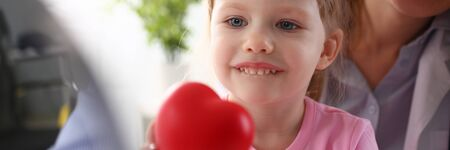 Little baby girl visiting doctor holding in hands red toy heart Imagens