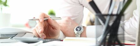 Hand of male clerk hold silver pen using calculator