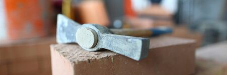 Focus on structure utensil lying on big red bricks. Smart man using helpful tool to make big and stable concrete wall made of hard blocks. Building concept Stock Photo
