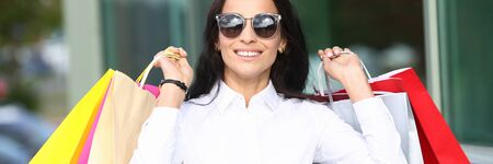 Portrait woman in sunglasses holding shopping bag Stockfoto - 128606658