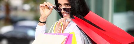 Portrait woman in sunglasses holding shopping bag Stockfoto - 128606659