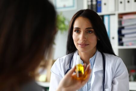 Pretty cheerful female GP giving medical marijuana oil to patient portrait