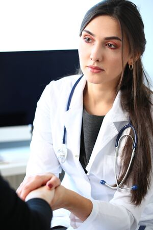 Young female doctor holds sick patient by hand expressing condolences and sympathy reports bad news about loss of loved ones due to cancer deadly aids disease and says we can handle support concept. Imagens