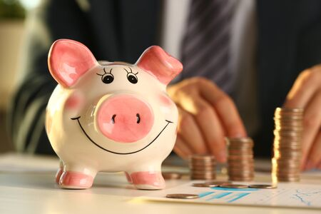 Hand businessman putting pin money into pig. Future needs loan education or mortgage credit spend vacation of dream effective buying financial risk and safety concept