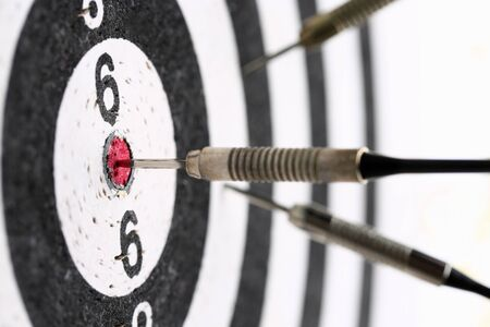 The dart game sticks out in the center of the red target an accurate hit to the target 스톡 콘텐츠