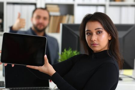 giovane bella donna bruna in ufficio lavora con il suo capo tenere il tablet in mano Archivio Fotografico