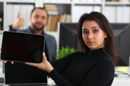 Joven bonita a mujer morena en el trabajo de oficina con su jefe mantenga tableta en manos Foto de archivo