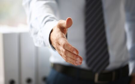 Man in suit and tie give hand as hello in office closeup. Friend welcome, mediation offer, positive introduction, thanks gesture, summit participate approval, motivation, male arm, strike bargain