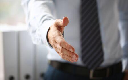 Mann in Anzug und Krawatte geben die Hand als hallo in der Büronahaufnahme. Freundliche Begrüßung, Vermittlungsangebot, positive Vorstellung, Dankesgeste, Zustimmung zur Gipfelteilnahme, Motivation, männlicher Arm, Streikhandel
