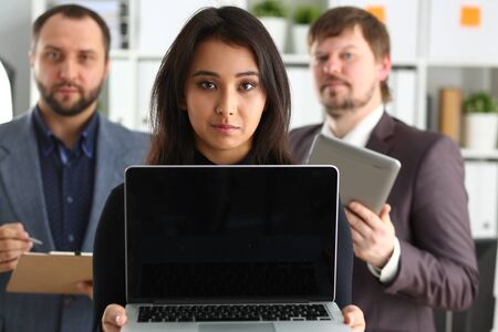 portrait of young successful businesslady hold laptop and two businessmen in office coworkers lovely job concept 免版税图像