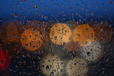 Blurred background of the night city rain drops on glass