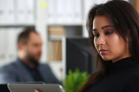 young pretty brunette woman in office work with her boss hold tablet in hands