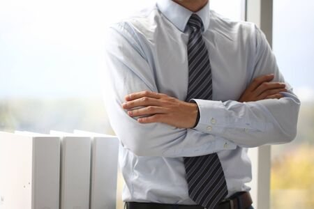Male hands in suit crossed on chest closeup background. White collar dress code modern office lifestyle graduate college study profession idea coach train election participation concept Stockfoto