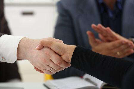 Junge glückliche Geschäftsleute treffen sich im Büro, schütteln sich die Hände und machen ein Erfolgskonzept