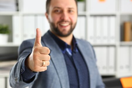 young handsome promising businessman work in office lend hand ahead show big finger up all right concept