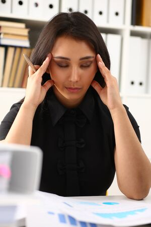 Tired and exhausted woman looks at documents propping up her head with her hands. Huge pile of document folders, headache and depression concept