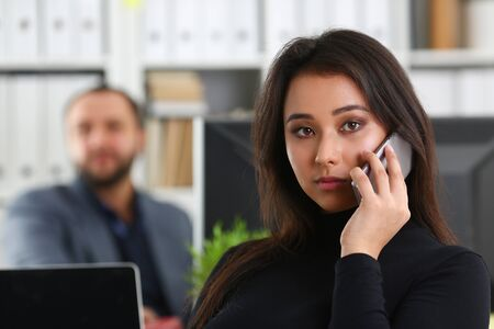 young pretty brunette woman in office work with her boss hold smartphone in hands talk to partners Stockfoto