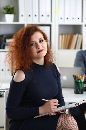 young beautiful red haired woman sit on chair at table in office in cabinet of her boss hold pen in arms work with documents