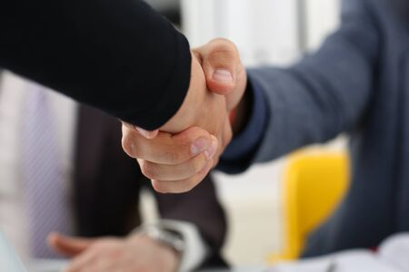 young happy businessmen have meeting in office shake hands with each other make success deal concept