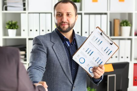 portrait of young handsome promising businessman work in office like his job handshake with business partner Фото со стока